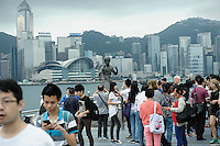 Crowd around statue of Bruce Lee, with Hong Kong skylinein background. Hong Kong, China