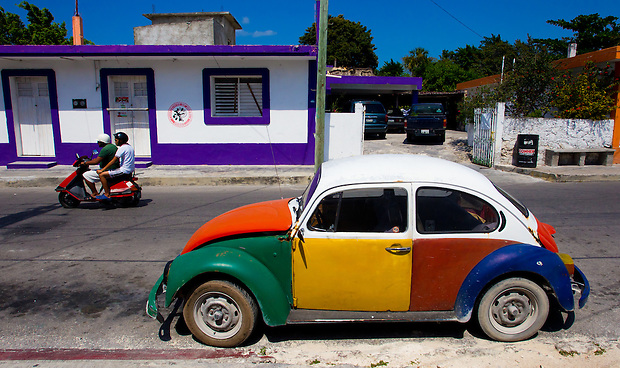A Volkswagen and scooter on a street in San Miguel de Cozumel, on the Mexican Island of Cozumel.