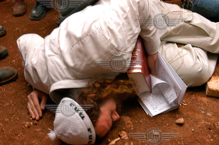 A Jewish settler clings to the ground during the demolition of a synagogue in the illegal Jewish outpost of Tapuach West. The synagogue was built in memorial to the late Rabi Kahana, former leader of the extreme Jewish right-wing, and is being demolished as part of the steps Israel is taking against illegal Jewish outposts.