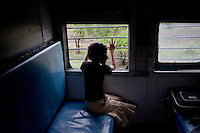 Anjali Lakhera aged 11 looks out the window as the train speeds through Madhya Pradesh to Maharashtra...Train passengers on the Himsagar Express 6318 going from Jammu Tawi station to Kanyakumari on 8th July 2009.. .6318 / Himsagar Express, India's longest single train journey, spanning 3720 kms, going from the mountains (Hima) to the seas (Sagar), from Jammu and Kashmir state of the Indian Himalayas to Kanyakumari, which is the southern most tip of India...Photo by Suzanne Lee / for The National