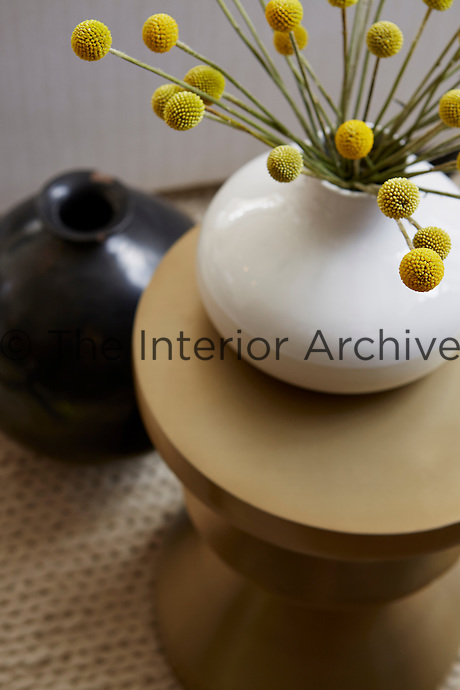 A simple flower arrangement is displayed on a gold side table.