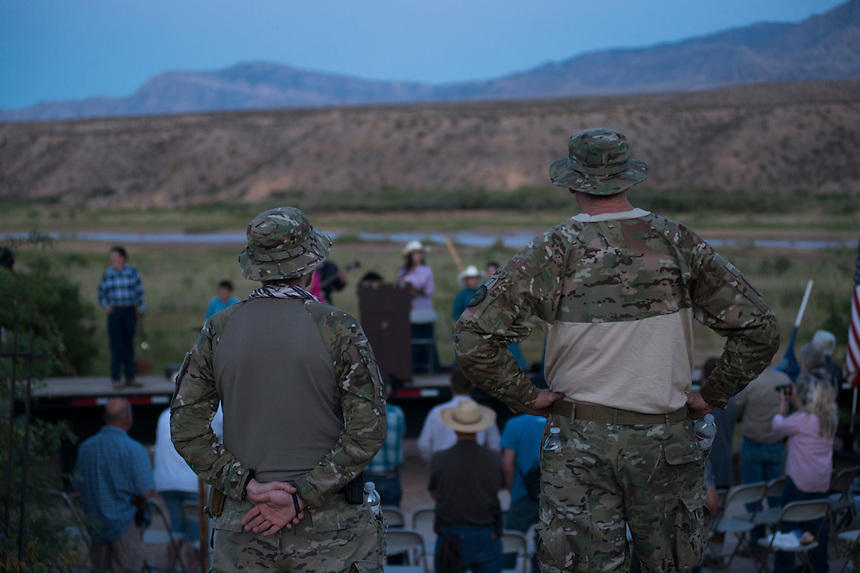 Two militia men listen the Sharp Family Singers, who traveled from Kansas to support Bundy, at a prayer gathering and cookout provided by Bundy for his supporters, near the Cliven Bundy ranch in Bunkerville, Nevada.<br /> <br /> Supporters of Bundy came from all over the country to defend against what they believe is government overreach.<br /> The Bundy standoff is a 20-year legal dispute between the United States Bureau of Land Management (BLM) and cattle rancher Cliven Bundy, over unpaid grazing fees, that recently provoked an armed confrontation between protesters and law enforcement.