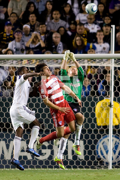 FC Dallas goalkeeper Kevin Hartman goes high over teammate George John and LA Galaxy forward Edson Buddle for a save preserving his clean sheet on the evening. FC Dallas defeated the LA Galaxy 3-0 to win the Western Division 2010 MLS Championship at Home Depot Center stadium in Carson, California on Sunday November 14, 2010.