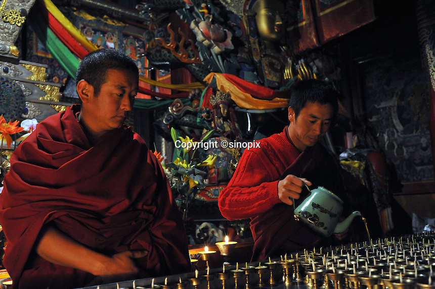 Monks fill butter lamps in Xia Qiong Temple, Qinghai, China. Qinghai Province in western China borders Tibet and parts were the scenes of disturbance earlier this year, 2008..12 Nov 2008
