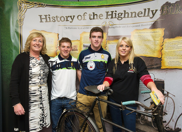 Marie Dillane and shop sales manager Danielle Dillane pictured with Clare senior hurlers Podge Collins and Tony Kelly during the launch of an exhibition  at Top Bike, Claureen, Lahinch Road, Ennis, which includes Michael Collin's bicycle, right, which he was regularly photographed with, during the War Of Independence. Photograph by John Kelly.