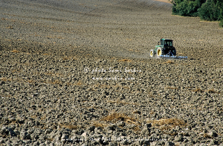 Tractor working in a dry, empty field in summer, Pamplona, Spain.