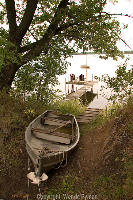 A row boat rests onshore, while 2 adirondack chairs on a dock look out on the deserted lake, White Bear Lake, MN.