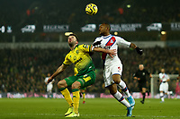 1st January 2020; Carrow Road, Norwich, Norfolk, England, English Premier League Football, Norwich versus Crystal Palace; Grant Hanley of Norwich City competes for the ball with Jordan Ayew of Crystal Palace - Strictly Editorial Use Only. No use with unauthorized audio, video, data, fixture lists, club/league logos or 'live' services. Online in-match use limited to 120 images, no video emulation. No use in betting, games or single club/league/player publications