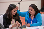 Fe Tangunan prays as she anoints the forehead of Jennifer Meneses with oil on January 17, 2018, during an international gathering of United Methodist Women in Manila.<br /> <br /> Both women are deaconesses. Tangunan is a former president of the National Clergy Spouse Associatoin, and Meneses is executive secretary  of the Board of Women's Work of the Philippines Central Conference.