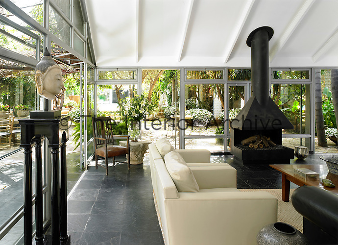 A spacious living room in a glass conservatory with a wood burning stove designed by Joshua Kastiel  Upholstered seating is set around a low wooden coffee table. Two boxy armchairs designed by Alex Meitlis are covered in a vinyl known in Israel as Prada plastic. The black fireplace designed by Joshua Kastiel dominates the space and contributes to the black-and-white palette.