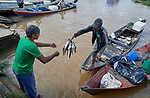 A fisher sells part of his catch at the dock in Santarem, a city alongside the Amazon River in Brazil's northern Para state.