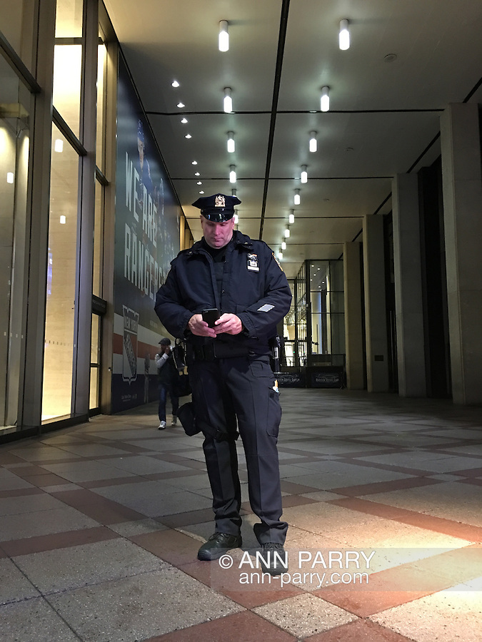 NYC, NY, USA. 19th Nov. 2015. At an outer entrance to Madison Square Garden, a NYPD (New York Police Department) officer is stationed, looking at his smart phone. Many tourists, workers, and law enforcement officers are seen throughout midtown Manhattan, the day after an ISIS propaganda video came out threatening New York City, particularly Times Square. NYC's Mayor and Police Commissioner both said there is no specific and credible threat against New York City.
