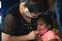 """Oltilia Zavala of Springdale (left) administers a covid-19 test to Selena Negron, 5, Sunday, June 28, 2020 at St. Raphael Catholic Church in Springdale. The Arkansas Department of Health partnered with the church to host a covid-19 screening for the parishioners of the church. Their goal was to administer 250 tests. """"They have a large Hispanic congregation greater than 70 percent so we're trying to offer it to their members,"""" said Cassie Cochran, Northwest Region Director. """"They're comfortable coming here, and it's convenient because they have eight masses on Sunday."""" The Arkansas Department of Health will hold another screening on Tuesday, June 30th at the Washington County Health Unit in Fayetteville that will be open to the general public from 4pm to 8pm. Check out nwaonline.com/200629Daily/ for today's photo gallery. <br /> (NWA Democrat-Gazette/Charlie Kaijo)"""