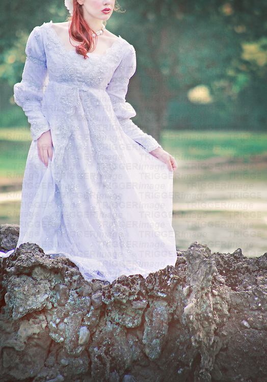 Faceless young brunette woman in a beautiful white wedding gown, standing on a romantic bridge outdoors