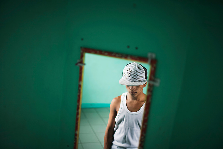 A teenage boy stands in his group home where he was moved after being imprisoned in an adult prison.