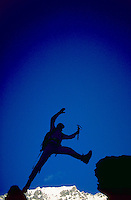 A silhouetted climber making a leap from one rock peak to another.