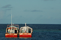 Two red fishing boats moored side by side in the blue ocean, Maldives.