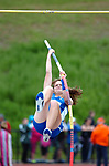 A female pole vaulter on her way over the bar.