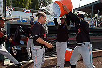 Batavia Muckdogs pitchers Edison Suriel (left) and Jonaiker Villalobos (right) dump the water cooler on pitching coach Chad Rhoades (15) after clinching the Pinckney Division Title during a NY-Penn League game against the Auburn Doubledays on September 2, 2019 at Falcon Park in Auburn, New York.  Batavia defeated Auburn 7-0 to clinch the Pinckney Division Title.  (Mike Janes/Four Seam Images)