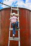 Jackson Kirkbride, 5, climbs up a ladder to check the water on storage tank as his father and uncle work to repair a wind powered water pump on the Harding and Kirkbride Ranch northeast of Cheyenne.  .