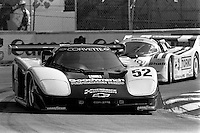 MIAMI, FL - MARCH 2: The Hendrick Motorsports Lola T710 HU1/Corvette GTP of  Sarel van der Merwe and Doc Bundy is driven ahead of the Brun Motorsport Porsche 962 107B of Massimo Sigala and Oscar Larrauri during the Lowenbrau Grand Prix of Miami IMSA GTP race on the temporary street circuit in Bicentennial Park in Miami, Florida, on March 2, 1986.
