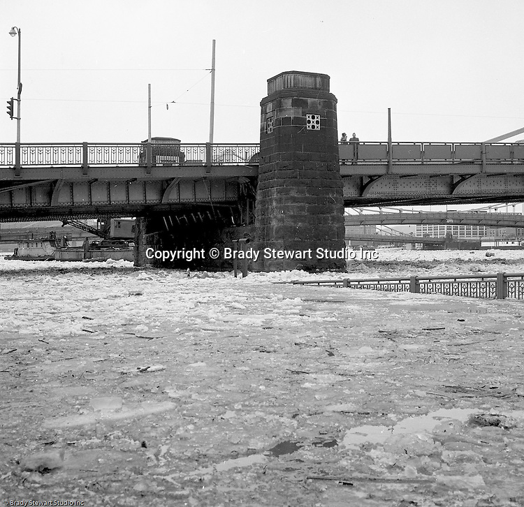 Pittsburgh PA:  High waters on the Allegheny River after a snow melt - 1959.  View of the water covering the 10th Street bypass in Pittsburgh. 9th Street Bridge in the background.