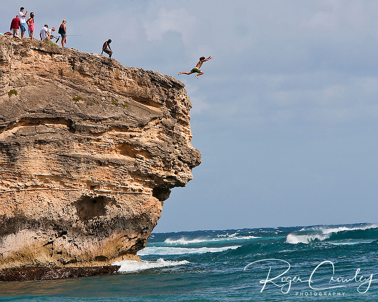 Cliff jumpers time the surf as they leap into the water near Shipwreck Beach on Kaua'i Hawaii.