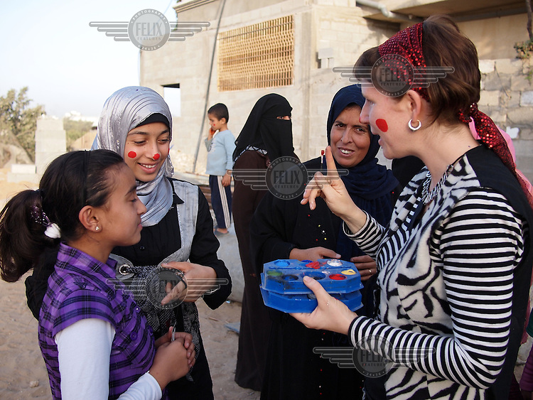 """Amira Al-Qerem (16, second from left) and her sister Haya get their faces painted in clown colours by a member of a visiting mini-circus from Manchester, England, in Gaza City on October 28 2010. Amira was missing and presumed dead after she was injured by one of the same explosions that killed her father, brother and sister during the last days of the Israeli invasion of Gaza in 2009. She was found three days later, after her family thought they had buried her remains with those of the other three. She is one of the main subjects of the controversial documentary film """"Tears of Gaza"""" by director Vibeke Løkkeberg."""