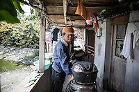 Li Jijun, a scrap collector and part-time manual laborer at his home in Xingxing village on the outskirts of Shanghai,  China on 14 August 2015.  As China's sputtering economy has beginning to affect employment, many migrants who used to live in the village to work on Shanghai's numerous construction sites and factories are beginning to thin out.