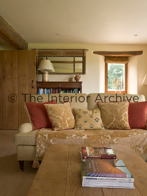 One of a pair of comfortable sofas in the living room is covered in restful beige and piled with cushions in varied floral fabrics