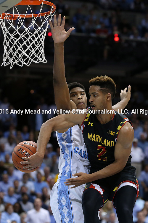 01 December 2015: Maryland's Melo Trimble (2) passes the ball behind North Carolina's Isaiah Hicks (left). The University of North Carolina Tar Heels hosted the University of Maryland Terrapins at the Dean E. Smith Center in Chapel Hill, North Carolina in a 2015-16 NCAA Division I Men's Basketball game. UNC won the game 89-81.