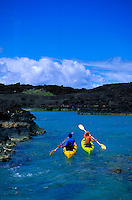 Man and woman kayaking in La Perouse Bay, the site of the last lava flow on Maui, on Maui's south side, south of Makena and near the Ahihi Marine Preserve. Rough black lava fields dominate this part of the south coastline as is seen behind the kayak