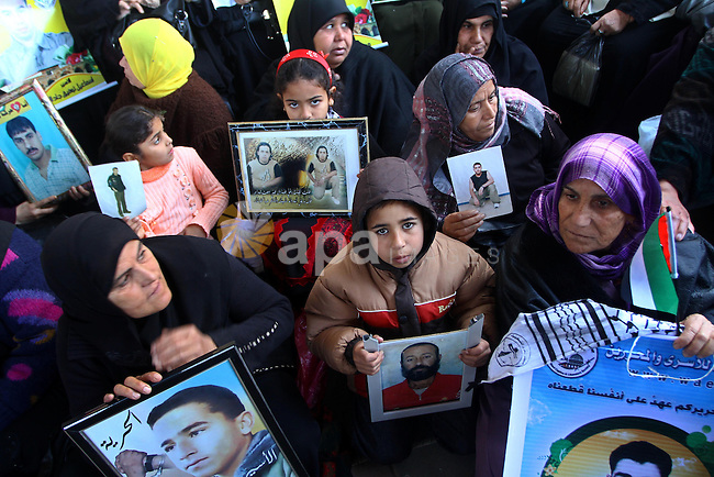 Palestinian women and children hold pictures of jailed relatives during a protest calling for the release of Palestinian prisoners from Israeli jails at the Red Cross office in Gaza City on Jan. 17, 2011. Photo by Ashraf Amra