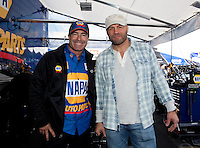 Feb 7, 2014; Pomona, CA, USA; NHRA funny car driver Ron Capps (left) poses for a photo with UFC fighter Randy Couture during qualifying for the Winternationals at Auto Club Raceway at Pomona. Mandatory Credit: Mark J. Rebilas-