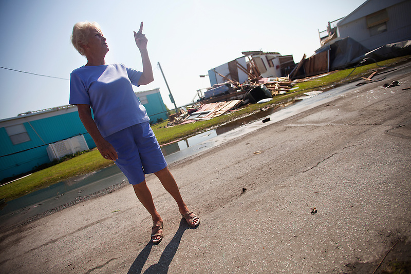 Rita Stevens of Atlantic Beach, surveys the damage to a mobile home in Triple S Marina Village, in Atlantic Beach, N.C. Stevens manages the park with her daughter. The trailer was demolished during the high winds and rain of Hurricane Irene, which made landfall in the area early Saturday morning. The majority of the trailers in this park sustained only minor damages, mostly to their roofs and awnings. Atlantic Beach was largely spared from the worst of the storm, but residents are likely to remain without power until crews can repair feeds to the area.