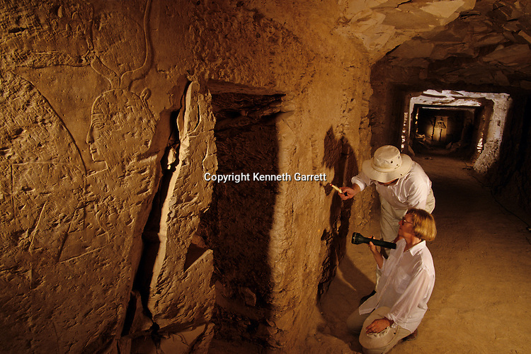 Valley of the Kings,Kent & Susan Weeks examine a 100 ft long hallway lined with doors & chambers in KV5 near Luxor, Egypt, reliefs of Hathor and Osiris