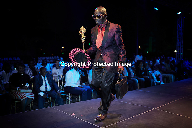 """KINSHASA, DRC - JULY 18: Sapeurs led by Papa Griffe walks on the catwalk at Kinshasa Fashion Week on July 18, 2014, at Shark club in Kinshasa, DRC. Local and invited foreign-based designers showed their collections during the second edition of Kinshasa Fashion week. in Kinshasa, DRC. The word Sapeur comes from SAPE, a French acronym for Société des Ambianceurs et Persons Élégants or Society of Revellers and Elegant People and it also means, to dress with elegance and style"""". Most of the young Sapeurs are unemployed, poor and live in harsh conditions in Kinshasa, a city of about 10 million people. For many of them being a Sapeur means they can escape their daily struggles and dress like fashionable Europeans. Many hustle to build up their expensive collections. Most Sapeurs could never afford to visit Paris, and usually relatives send or bring clothes back to Kinshasa. (Photo by Per-Anders Pettersson)"""