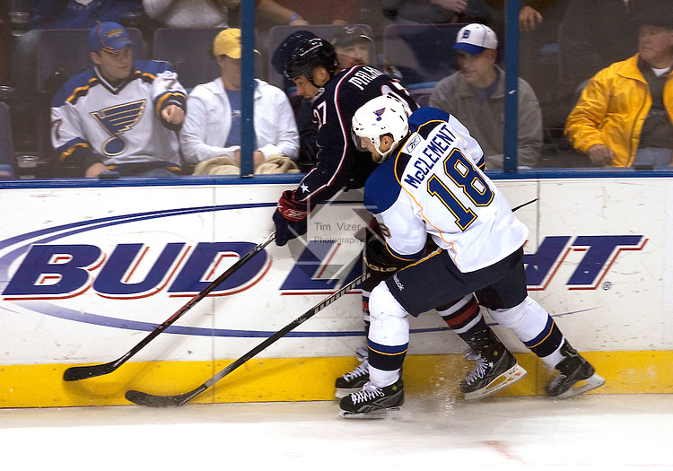 March 28 2009       The Blue Jackets Manny Malhotra (27, left) is slammed against the boards by the Blues Jay McClement (18) in first period action.  The St. Louis Blues hosted the  Columbus Blue Jackets March 28, 2009 at the Scottrade Center in downtown St. Louis, Missouri...            *******EDITORIAL USE ONLY*******