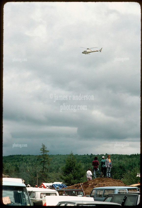 Helicopter Arriving at the Grateful Dead Concert, Oxford Speedway Maine on 2 July 1988. The Deadhead Campground Scene with fans standing on a dirt mound for a better view. Pine woods in the background, cars, vans, parking in foreground. Cloudy sky. Chopper probably transporting some members of the Band.