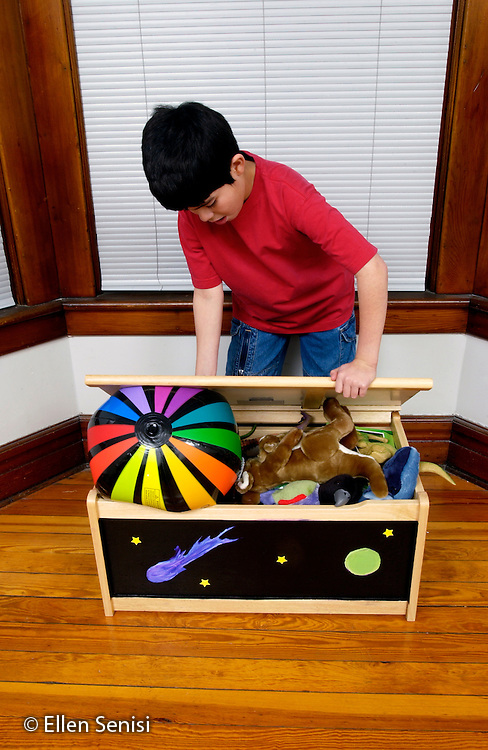 MR / Schenectady, NY.Boy (9, Paraguayan-American) tries to close toy box that is too full of toys..MR: Thi2.©Ellen B. Senisi