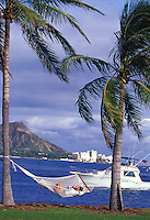 Woman relaxing in hammock between palm trees while talking on a cell phone, with Diamond Head in background