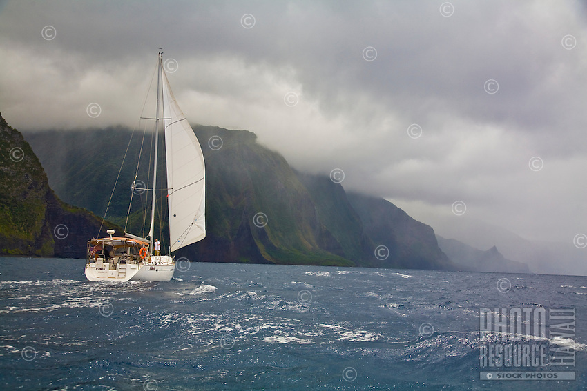 Cruising yacht sailing downwind along the vertical sea cliffs of Molokai, Hawaii