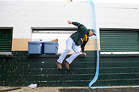 Photo By Kristin Eberts: Don Cooley, Treasurer of the Athens High School Athletic Boosters, jumps out of the concession stand window while working on cleanup at Basil Rutter Field at Athens High School on the morning of Friday, Sept. 17, 2010 in The Plains, Ohio. An unconfirmed tornado ripped through The Plains, Ohio Thursday Sept. 16, 2010, causing downed power lines, uprooted trees, overturned mobile homes and significant damage to Athens High School.