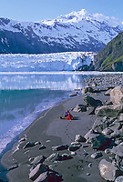 Tourists relax on black sand beach in Barry Arm, Barry glacier, Chugach mountains, Prince William Sound