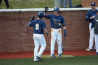 McCann Mellett (9) of the Wingate Bulldogs is congratulated by teammate Jed Bryant (12) after scoring a run against the Concord Mountain Lions at Ron Christopher Stadium on February 1, 2020 in Wingate, North Carolina. The Bulldogs defeated the Mountain Lions 8-0 in game one of a doubleheader. (Brian Westerholt/Four Seam Images)