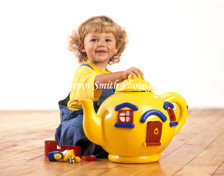 Smiling young girl playing with a very large toy teapot.