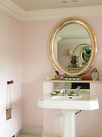 A gilt-framed oval-shaped mirror above the basin in the bathroom reflects a series of other mirrors