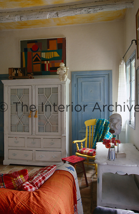 An abstract painting hangs above the white cabinet in a sitting room that is filled with eclectic furniture and objects