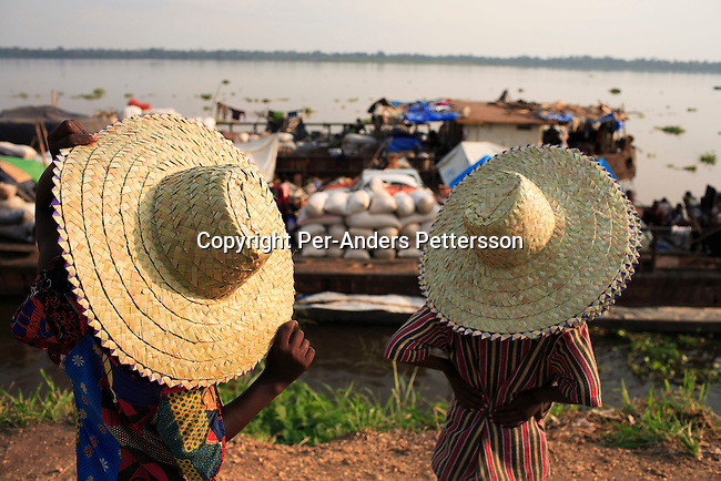 BUMBA, DEMOCRATIC REPUBLIC OF CONGO MARCH 25: Two girls sell straw hats in the port on March 25, 2006 in Bumba, Congo, DRC. The girls are trying to sell hats to passengers traveling on a boat from Kisangani to Kinshasa, a journey of 3-7 weeks. Congo River is a lifeline for millions of people, who depend on it for transport and trade. During the Mobuto era, big boats run by the state company ONATRA dominated the traffic on the river. These boats had cabins and restaurants etc. All the boats are now private and are mainly barges that transport goods. The crews sell tickets to passengers who travel in very bad conditions, mixing passengers with animals, goods and only about two toilets for five hundred passengers. The conditions on the boats often resemble conditions in a refugee camp. Congo is planning to hold general elections by July 2006, the first democratic elections in forty years..(Photo by Per-Anders Pettersson/Getty Images)..