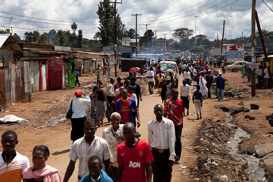 People throng the main street outside the Madiaba Busaa club in a Nairobi slum on April 14, 2013. Busaa, a traditional fermented beer, is made by crudely fermenting maize, millet, sorghum or molasses. At Kshs 35 per liter it is much cheaper than a Kshs120 half-liter bottle of commercial beer. The local brew was legalised in 2010 and since then Busaa clubs have become increasingly popular in slums and rural areas. Drinking is on the rise in Kenya, especially among young people. Photo by Benedicte Desrus